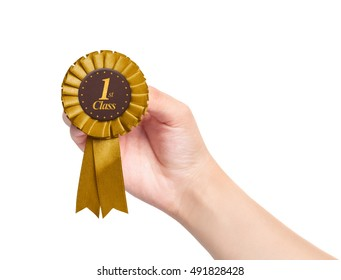 hand holding golden first class rosette on white background