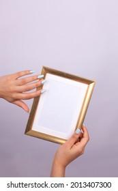 hand holding golden frame, beauty manicure light blue nail polish - Shutterstock ID 2013407300