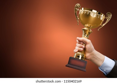 Hand holding golden trophy on blurred background