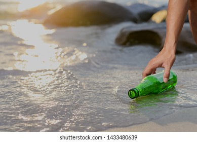 Hand holding green beer bottle on the beach,Concept of pollution control of the seas and oceans by plastic. Beat Plastic Pollution.