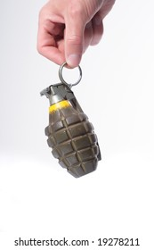 A hand holding a green combat pineapple grenade hanging by the trigger.