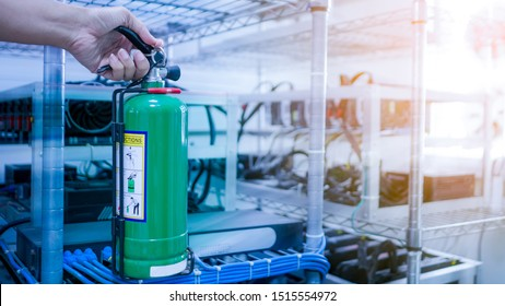 Hand holding green fire extinguisher, blur background is bitcoin mining machine. Concept  Fire extinguishers for electrical and electronic appliances