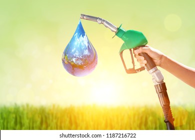 Hand holding a Green Green gas nozzle  on Green nature background.