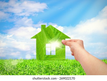 hand holding green house with field and blue sky background. Eco house concept