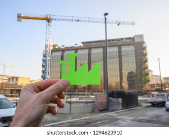 Hand holding a Green Industry sign against construction site.