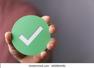 A hand holding a green paper with the checkmark sign on it