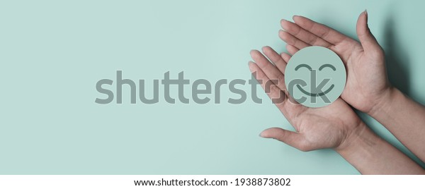 Hand holding green paper cut smile face on green background, positive thinking, mental health assessment , world mental health day concept