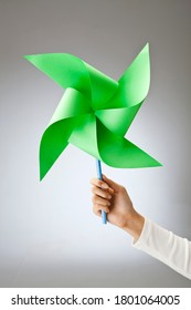 hand holding a green pinwheel in one hand