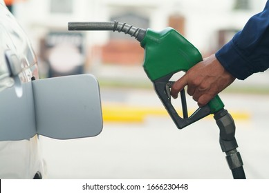 hand holding a green pistol for automatic petrol pump