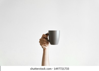 Hand holding a grey cup of coffe om white background. Concept of sleepy morning. Copy space