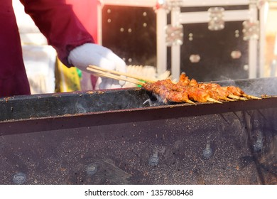 A hand holding grilled meat in sticks over the charcoals with smoke.