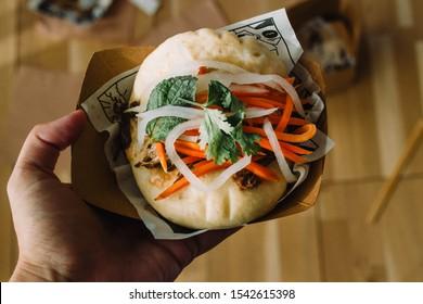 Hand holding gua bao, hirata buns, bao buns, guabao or baozi (traditional asian sandwich). Chinese food from Fuzhou, named Cha bao in Hong Kong and kakuni manju in Japan. Flatlay instagram style