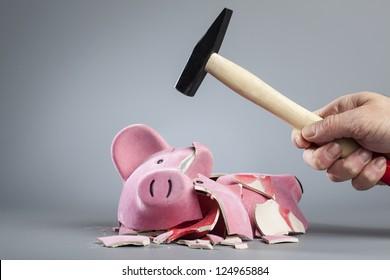Hand holding hammer over a broken piggy bank.