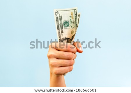 A hand holding a handful of twenty us dollars, on blue background.