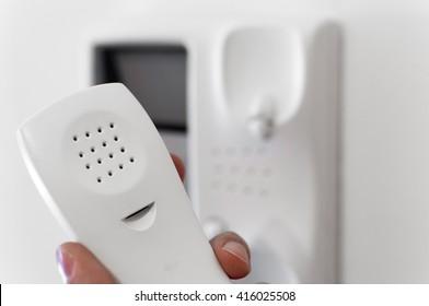 Hand holding headphone of entry phone.
