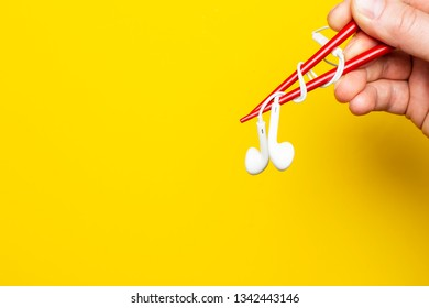 Hand  is holding a headphones using chopsticks on a bright yellow background, with copy space. Cconcept of musical taste. Close-up.