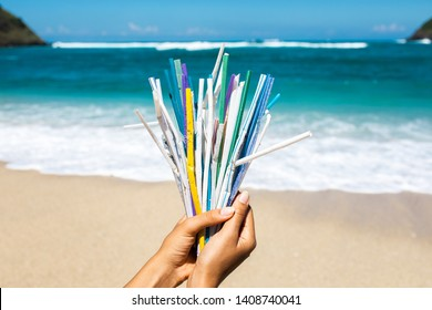 Hand holding heap of used plastic straws on background of clean beach and ocean waves. Plastic ocean pollution, environmental crisis