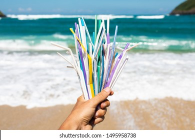 Hand holding heap of used plastic straws on background of clean beach and ocean waves. Plastic ocean pollution, environmental crisis. Say no plastic. Single-use plastic waste