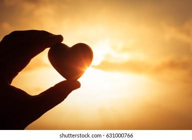 Hand holding heart against a golden sunset.