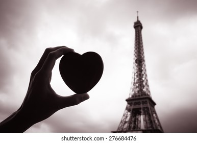 Hand holding heart next to the Eiffel tower.