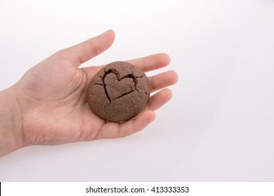 Hand holding a heart patterned chocolate cookie on a white background