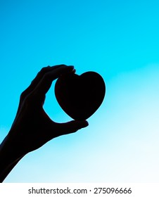 Hand holding heart to the sky.