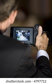 A videographer's hand holding his camera with focus on the bride and groom.