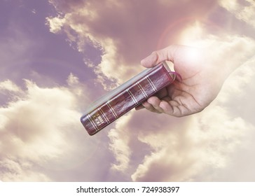 Hand holding Holy Bible throughout cloudy sky with lens Flare shows Christian symbol that God has given his word to humans in the Holy Bible
