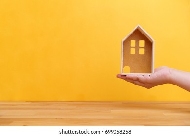 Hand holding home model with wooden table and yellow background for house ownership or real estate business concept