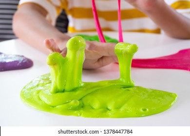 Hand Holding Homemade Toy Called Slime, Sibling boy and girl having fun and being creative by science experiment.
