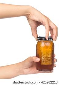 hand holding honey jar isolated on white background