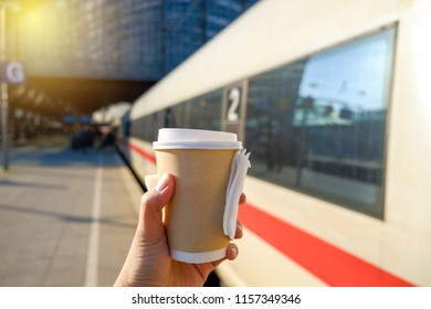 Hand holding hot coffee cup in morning at train station.