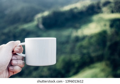 Hand holding hot coffee cup at green blur mountain nature forest,Leisure lifestyle