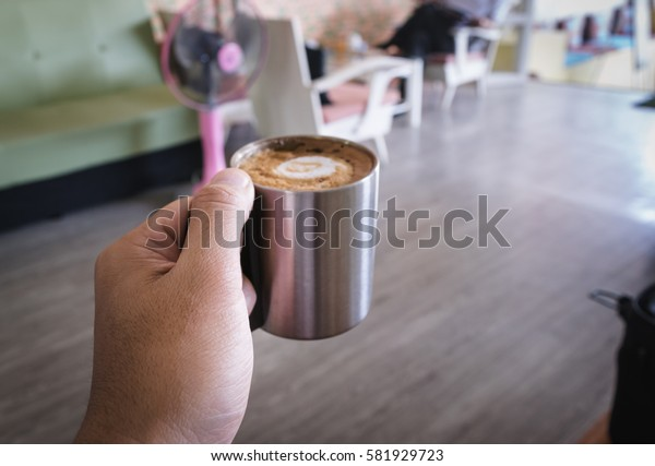 Hand  holding hot dark coffee in stainless cup in asian coffee shop. Dark coffee concept.