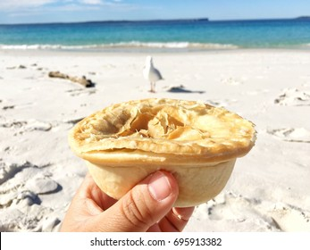 Hand holding a hot meat pie at the beach in Jervis Bay national park with bird, sea and blue sky on background.