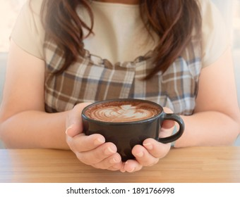 hand holding hot organic cocoa with foam froth art in black ceramic cup