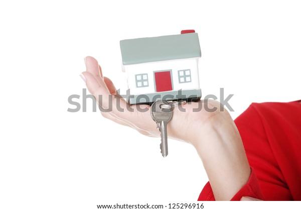 Hand holding a house key. Isolated on white background.