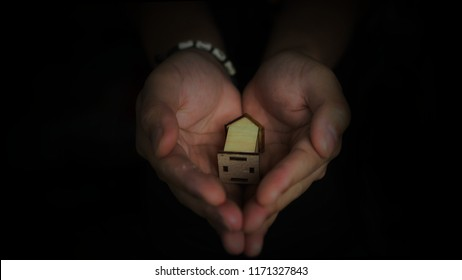 hand holding house model with black background, finance concept