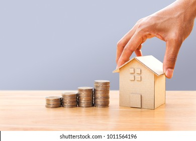 Hand holding house model and money stack on wooden table. Concept for property ladder, mortgage and real estate investment. Investment and business growth concept
