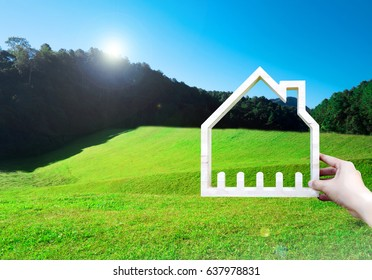 Hand holding house model on a green meadow and mountain scenery, Build a house on vacant land concept
