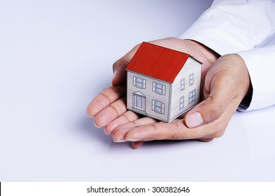Hand holding house paper for Mortgage loans concept
