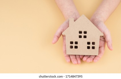 Hand holding house small on yellow background. Home safety plan is an essential tool for keeping your family safe. top view.   copy space.
