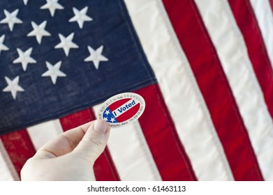 "Hand holding an ""I voted"" sticker in front of the American Flag"