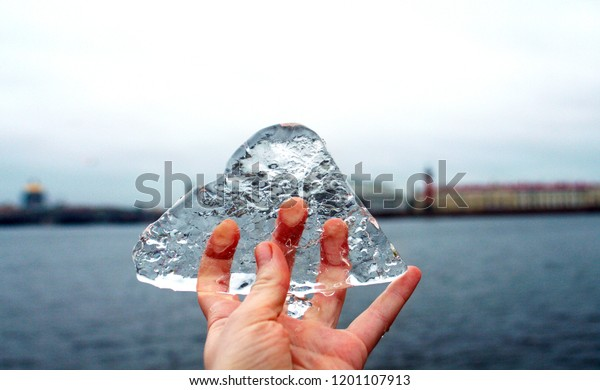 Hand holding ice on the city and river background. First snow in early winter. Cold weather concept.