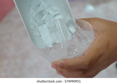 A hand holding in  the ice scoop on a lot of ices with plastic glass.