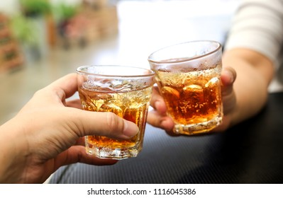 hand holding ice whisky glass, clinking glasses, alcoholism problem