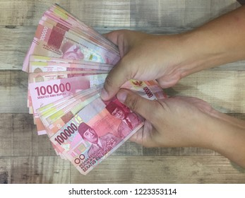 Hand holding Indonesian rupiah money notes