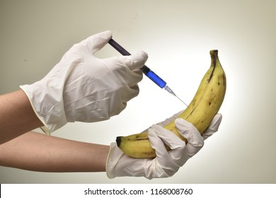 hand holding injection ( pesticides)  on the fruit banana
