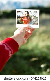 Hand holding an instant photo of a girl happy
