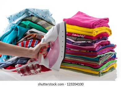 Hand holding iron with colorful laundry